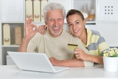 boy and  grandfather with a laptop and credit card Royalty Free Stock Photo