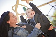 Portrait of boy hangs by horizontal bar with mother Stock Images