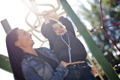 Portrait of boy hangs by horizontal bar with mother Stock Photos