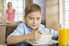 Portrait of boy having breakfast at table with mother standing in background Royalty Free Stock Images