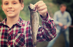 Portrait of boy having fish in hands Stock Photo