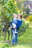 Portrait of boy with his baby sister in vine yard. Portrait of a boy holding his little baby sister playing in a beautiful vine yard Stock Photos