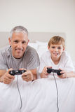 Portrait of a boy and his father playing video games Stock Image
