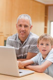 Portrait of a boy and his father using a laptop. In their kitchen royalty free stock photo