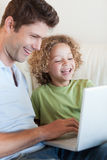 Portrait of a boy and his father using a laptop. Portrait of a cute boy and his father using a laptop in their living room royalty free stock photo