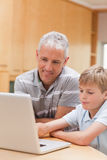 Portrait of a boy and his father using a notebook Stock Photos