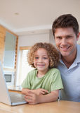 Portrait of a boy and his father using a notebook Stock Image