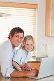 Portrait of a boy and his father using a notebook together Royalty Free Stock Photo