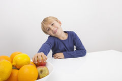 Portrait of boy holding apple from fruit bowl at table Royalty Free Stock Images