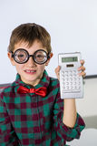 Portrait of boy holding calculator in classroom Stock Image