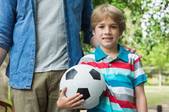 Portrait of a boy holding football besides his father Stock Photography
