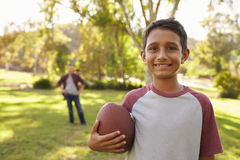 Portrait of boy holding football in park, dad in background Royalty Free Stock Photography