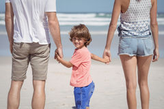 Portrait of boy holding hands with parents at beach Stock Photo