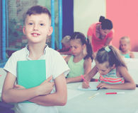 Portrait of boy holding notepad in school class. Portrait of cheerful russian boy holding notepad in school class Royalty Free Stock Photo