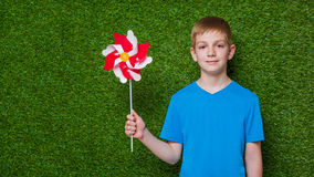 Portrait of a boy holding pinwheel over grass Stock Image