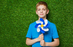 Portrait of a boy holding pinwheel over grass Royalty Free Stock Images