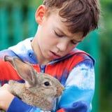 Portrait of boy, he is holding rabbit Stock Photos