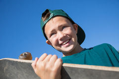 Portrait boy holding a skateboard. Portrait of a happy boy holding a skateboard Stock Images