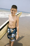 Portrait of boy holding surfboard on beach Royalty Free Stock Images