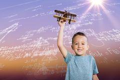 Composite image of portrait of boy holding toy airplane. Portrait of boy holding toy airplane against sunrise sky Royalty Free Stock Photo