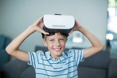 Portrait of boy holding virtual reality headset in living room Royalty Free Stock Photos