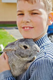 Portrait of boy that holds rabbit in hands. Closeup portrait of boy that holds rabbit in hands stock image