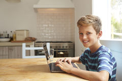 Portrait Of Boy At Home Using Laptop On Kitchen Table Royalty Free Stock Photos