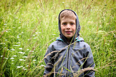 Portrait of the boy with hood standing in the very high grass Stock Photography