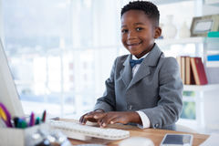 Portrait of boy imitating as businessman using computer Royalty Free Stock Photography