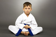 Portrait of a boy in kimono training on the floor. Isolated over gray background Royalty Free Stock Photos