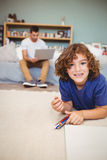 Portrait of boy lying on floor while father working in background Stock Photo