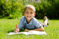 Portrait of a boy lying on the grass with a book Stock Photography