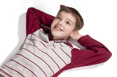 Portrait of a boy lying on a white floor Royalty Free Stock Image
