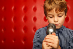 Portrait of boy with microphone against red wall Royalty Free Stock Photo