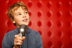 Portrait of boy with microphone on rack Royalty Free Stock Photo