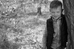 Portrait of Boy Outdoors Leaning Against Tree Royalty Free Stock Image