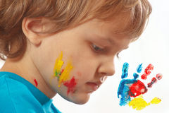 Portrait of a boy with painted face on a background of hand printsPortrait of a boy with painted face on background of hand prints stock images