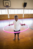 Portrait of boy playing with hula hoop in school gym Royalty Free Stock Image