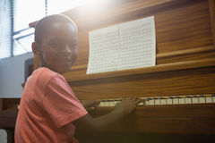 Portrait of boy playing piano in classroom Stock Photography