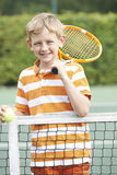 Portrait Of Boy Playing Tennis Standing Next To Net. Boy Playing Tennis Standing Next To Net Stock Photography