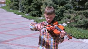 Portrait of boy is playing the violin standing in the alley on the street. Child boy is playing violin standing in alley on street in city. Portrait of little stock video