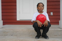 Portrait of boy on porch. A picture of a boy sitting on steps with ball Royalty Free Stock Photo