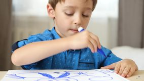 Portrait of a boy of preschool age. The child sits at the table and paint a bright blue felt pen on paper. stock footage