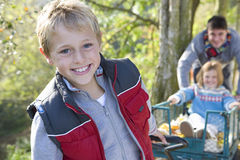 Portrait of boy pulling wheelbarrow, father and sister in background Royalty Free Stock Photography