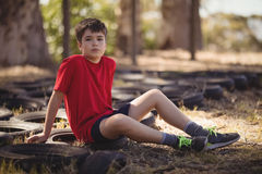 Portrait of boy relaxing on tyre during obstacle course. During obstacle course in boot camp Stock Photo