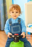 Portrait of a boy riding a toy car Stock Photo