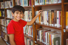 Portrait of boy selecting book in library Royalty Free Stock Photography