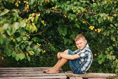 Portrait of a boy in a shirt and shorts in the orchard . Barefoot boy sitting near apricot stock photography