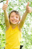 Portrait of a boy showing thumbs up. Spring portrait of a happy boy showing thumbs up outdoors Royalty Free Stock Photo