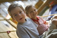 Portrait of a boy sitting with his friend on a rope climbing net Stock Images